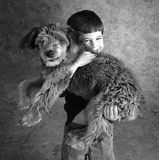 young boy carrying pet dog